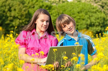 Two Smiling teenagers with laptop on meadow full of yellow flowe