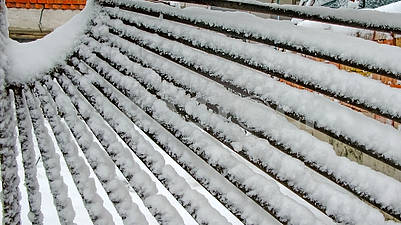 Snow on a metal fence made of rods.