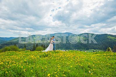 Wedding in mountains, A COUPLE IN LOVE, MOUNTAINS background, STANDING surounded dandelions, AMONG THE LAWN WITH THE GREEN GRASS, RUSTIC STYLE, GIRL IN LONG TULLE DRESS, romantic landscape