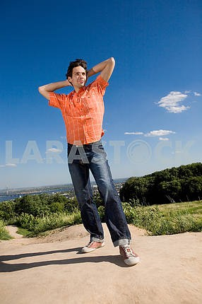Young man winning on peak of a mountain. Against a blue sky with