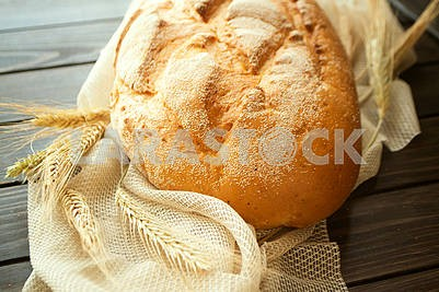 Golden rustic crusty loaves of bread on black rustic background.