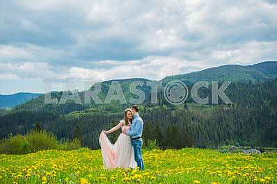 Wedding in mountains, a couple in love, mountains background, standing surrounded dandelions, among the lawn with the green grass, rustic style, girl in long tulle dress, romantic landscape