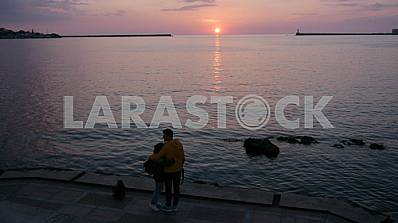 Couple admiring the sunset from the embankment in Sevastopol