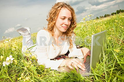 Young woman sitting on the grass field with a laptop. Against th