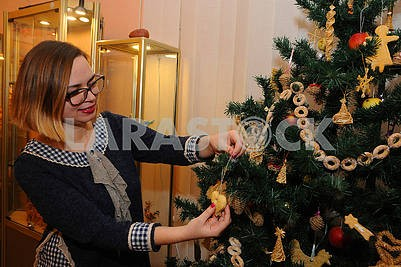 Woman decorates the Christmas tree