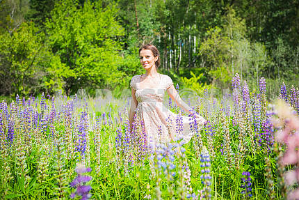 Young woman, happy, standing among the field of violet lupines, smiling, purple flowers. Blue sky on the background.