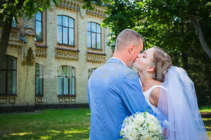 bride and groom, on the street, green tree and architecture building on the background, woman is kissing the man, wedding day