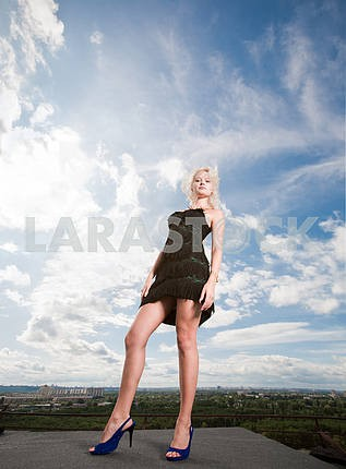 Beautiful girl stending against a cloudy sky