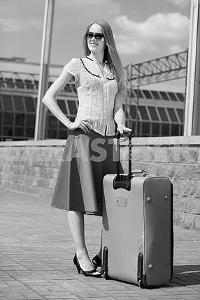 Smiling sexy blonde girl with suitcase