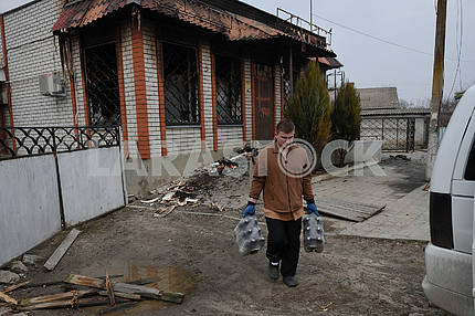 A man takes bottles from a destroyed store in Balakley
