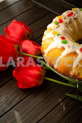 Easter yeast cake or babka covered with icing and decorated with colorful decoration on a dark wooden table and bright tulips