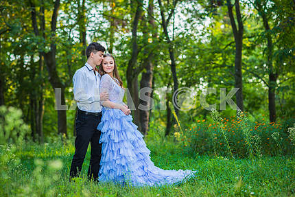 a love story couple, in love, together in the forrest park, girl in a beautiful violet dress, sunny evening, summer, thematic wedding shooting, frill dress