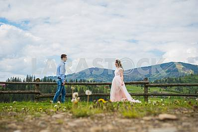 Newlyweds - handsome groom and gorgeous bride walking on trail across field with forest hills and cloudly sky as background, old wooden fence