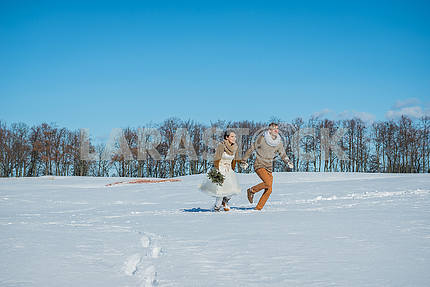 a wedding couple walking on the snowed field on a sunny day  rustic style wedding brown colors and white wedding dress