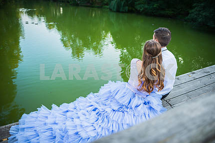 A love story couple, in love,  sitting back,  together in the forrest park, sitting  on the wooden bridge, girl in a beautiful violet dress, sunny evening, summer, green water on the background