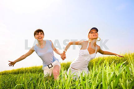 Two beautiful women in white clothes go to the yellow flowers