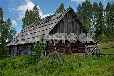 Lonely old wood house on a mountain hill against cloudy sky.