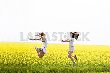 Two beautiful girl in white clothes jumps the yellow flowers
