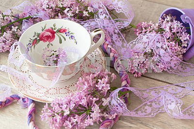 Vintage cup of tea with violet blooming branch of lilac, retro background for invitation, greeting card, design.