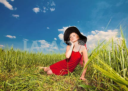 Happy young woman sitting on grass in hat