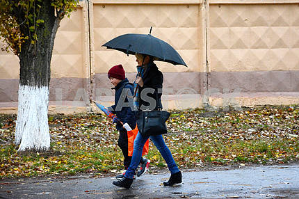 A woman and a boy go under an umbrella