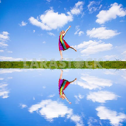 Happy girl jumping together on green meadow. Reflected in water