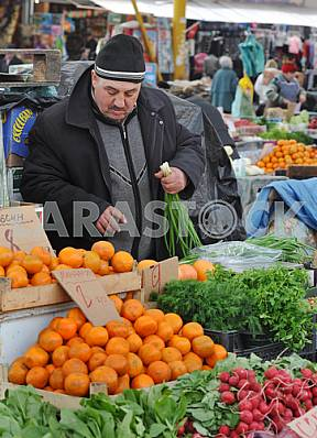 """Man sells tangerines and greens on the market """"Privoz"""" April 6, 2012"""