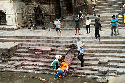 The relatives washed the feet of the deceased in the holy river