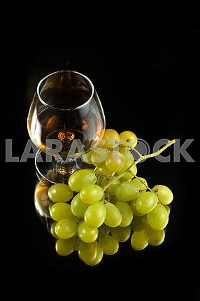 Glass of brandy and grapes