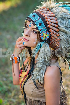 Young woman dressed in an Indian style in the woods Portrait of a young lady in the Indian roach