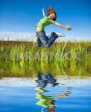 Happy young woman is jumping in a field