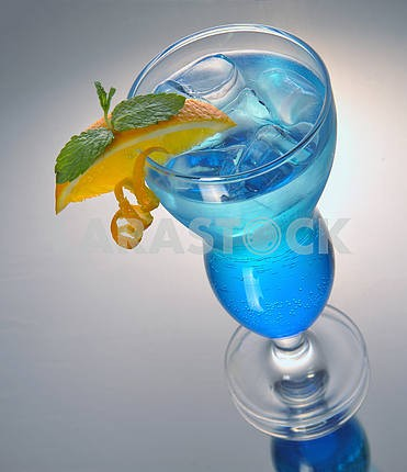 blue cocktail with ice and orange