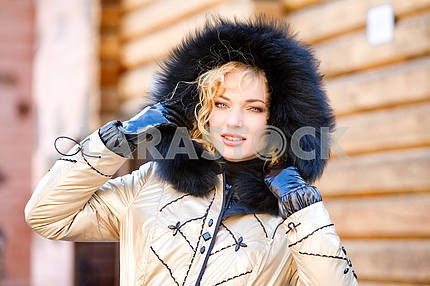 Portrait smiling young woman with a fur hood. Photography for fa