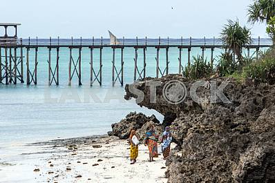 Zanzibar, people go along the shore along the water