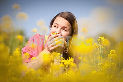 Pretty smiling girl relaxing on green meadow full of yellow flow