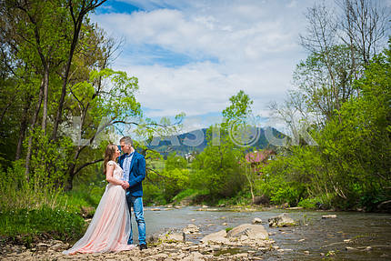 Wedding in mountains, a couple in love, mountains background, standing surrounded river, among the rocks, rustic style, girl in long tulle dress, romantic landscape,