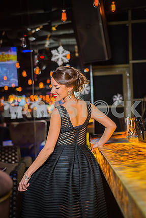 Beautiful brunette woman walking out in the restaurant, in black dress and red shoes. Smiling with her red lips, shy like a little girl showing her back