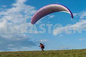 Параплан летит над горами в летний день