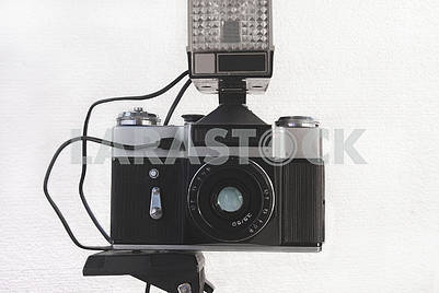 Old Soviet film camera on a tripod with a flash and a lens on a