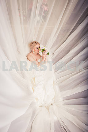 Blonde Bride in bathroom surrounded with the veil, felling the smell of bouquet