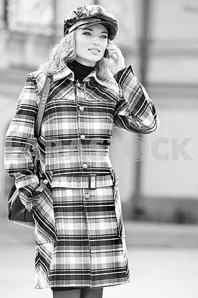 Beautiful young blond in a coat talks on the phone. Photography