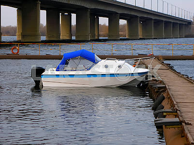 White motor boat stands near the pier, in the dock