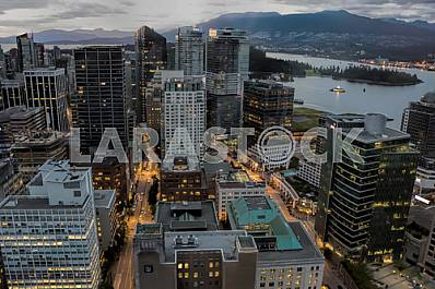 Vancouver-city at night at dusk overlooking the bay.