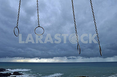 Gymnastic rings on the beach against the background of a thunderstorm sky