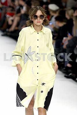 Model in a yellow raincoat demonstrates outfit by Ukrainian designer Larisa Lobanova