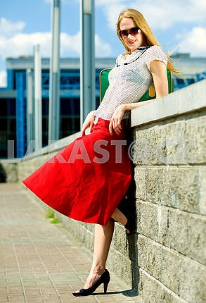 Smiling sexy blonde girl wearing red skirt. In all growth. Near