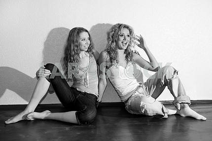 Two attractive young women sitting close on hardwood floor in ho