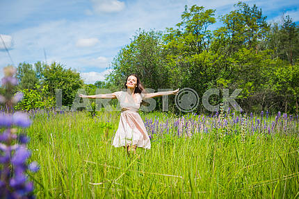 Young woman, happy, standing among the field of violet lupines, smiling,