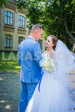 bride and groom looking into each other, on the street, green tree and architecture building on the background, weil is fluttering with the wind, wedding day
