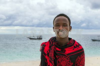 Zanzibar, young man on the beach near the water